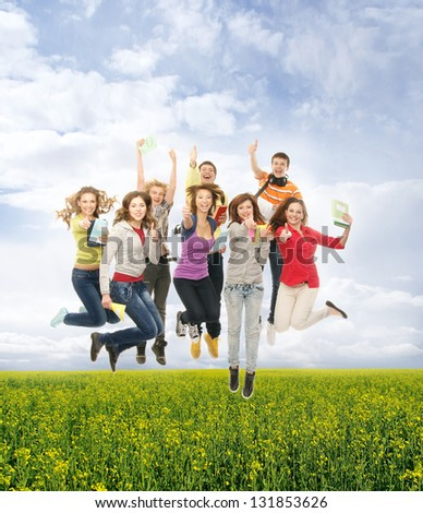 Group of smiling teenagers jumping together and looking at camera over the summer background - stock photo