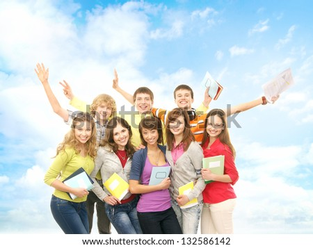 Group of smiling teenagers staying together and looking at camera over the summer background - stock photo