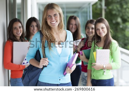 Group of smiling teenagers with folders and school bags  - stock photo