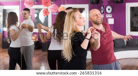 Group of smiling young adults dancing salsa at dance class. Focus on girl - stock photo