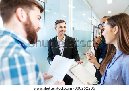 Group of smiling young business people standing and talking with team leader in hall of office - stock photo