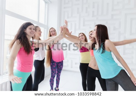 Group of smiling young women wearing sportswear joining hands together. Women power concept