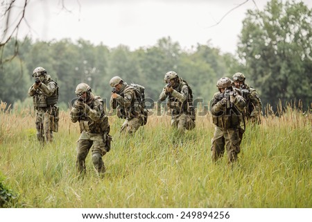 group of soldiers running across the field and shoot - stock photo