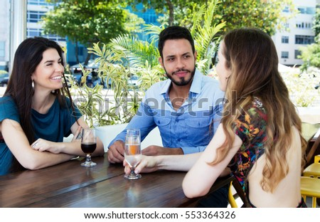 Group of speaking man and woman in a bar
