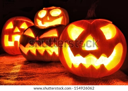 Group of spooky Halloween Jack o Lanterns lit at night - stock photo