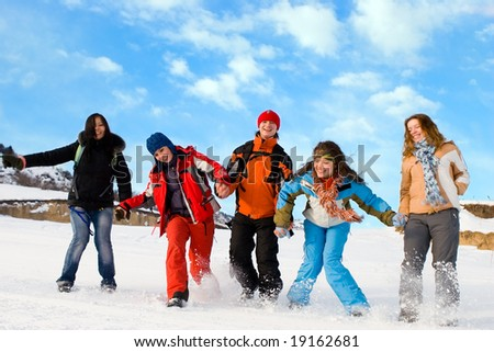 Group of sport teens different ethnicity jumping winter outdors at mountain Tien Shan. One boy and four girls.