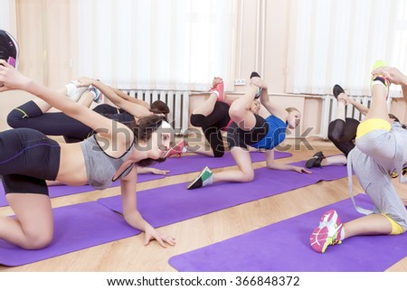 Group of Sportive Caucasian Women Stretching Indoors on Sport Mats. Horizontal Shot - stock photo