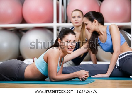 Group of sportswomen have a rest in the gym centre against set of colorful balls - stock photo