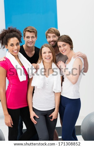 Group of sporty diverse multiethnic young people at the gym posing together after their workouts with their towels around their shoulders - stock photo