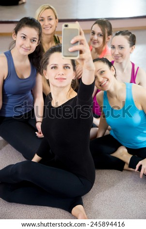 Group of sporty female friends using mobile phone, taking picture, selfie, self-portrait with smartphone while resting after practice, on break between exercises in sports club