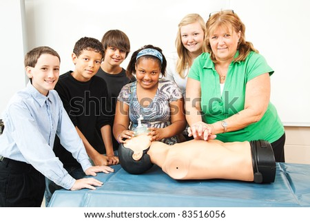 Group of students and their teacher, learning CPR in school. - stock photo
