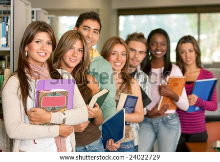 Group of students at a library smiling and holding some notebooks - stock photo