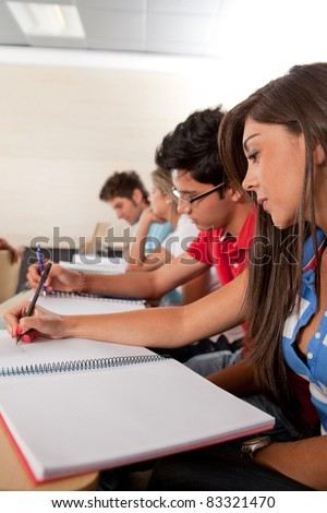 Group of students at the university inside a classroom studying - stock photo