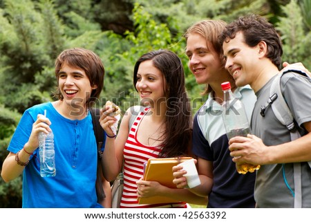Group of students during a lunch break in park - stock photo