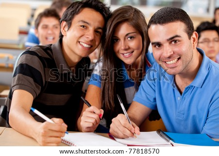 Group of students in a university classroom with notebooks - stock photo