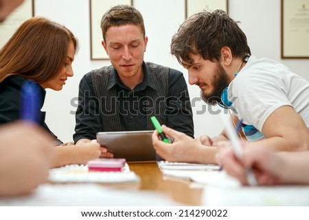 Group of students in classroom with electronic tablet - stock photo