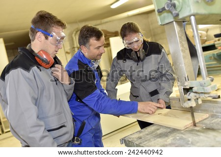 Group of students learning how to use woodwork machine - stock photo