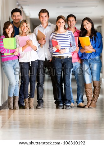 Group of students looking happy at the university hallway - stock photo
