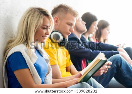 Group of students on a break reading books and using smartphones. Focus on a happy teenage girl. Background is blurry. - stock photo