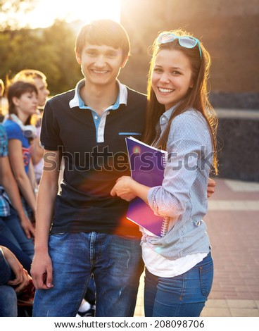 Group of students or teenagers with notebooks outdoors in summer evening - stock photo