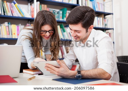 Group of students reading a book in a library - stock photo