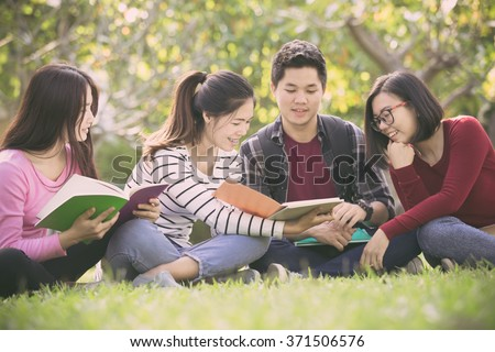 Group of students sharing with the ideas on the campus lawn - stock photo