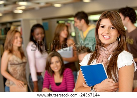 Group of students standing at the library smiling - stock photo