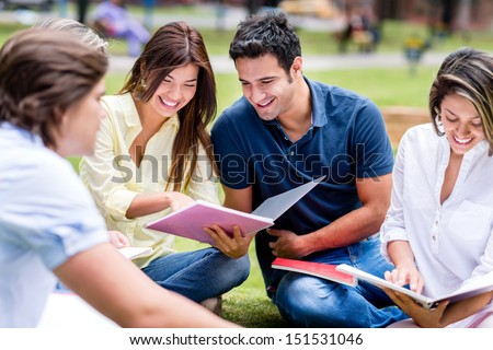 Group of students studying outdoors and looking very happy - stock photo