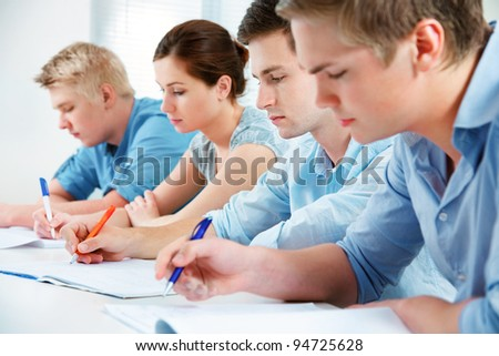 group of students studying together in classroom - stock photo
