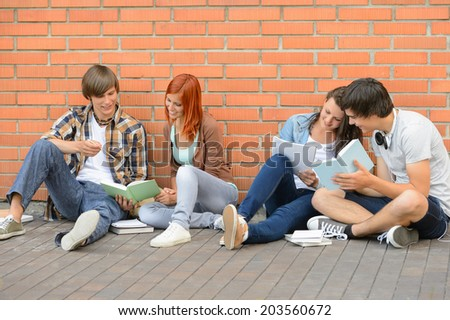 Group of students with books hanging out sitting against wall - stock photo