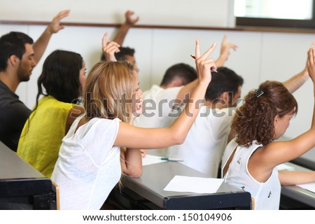 group of students with hands up - stock photo