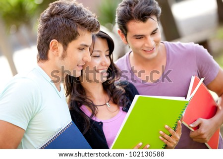Group of students with notebooks smiling outdoors