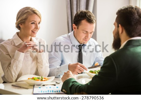 Group of successful business people at business lunch in cafe. - stock photo