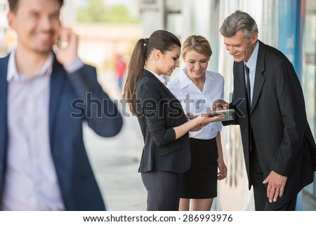 Group of successful business people in suits using digital tablet. Office background.