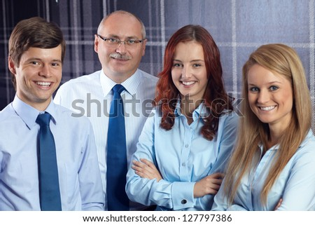 Group of successful happy smiling business people standing together in the office - stock photo