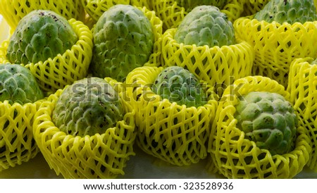Group of Sugar Apples (custard apple, Annona, sweetsop) in protective wrapper on display at the fruits stall in Singapore. They have vitamin C, thiamine, potassium, and dietary fiber. Panoramic style - stock photo