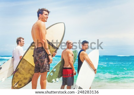 group of surfers on a beach - stock photo