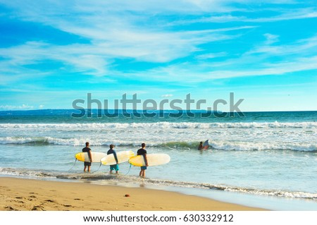 Group of surfers ready to surf on the beach. Bali island, Indonesia