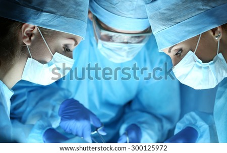 Group of surgeons at work operating in surgical theatre. Resuscitation medicine team wearing protective masks holding steel medical tools saving patient. Surgery and emergency concept - stock photo