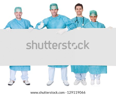 Group of surgeons presenting empty banner. Isolated on white - stock photo