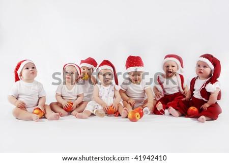 Group of sweet babies wearing christmas hats - stock photo
