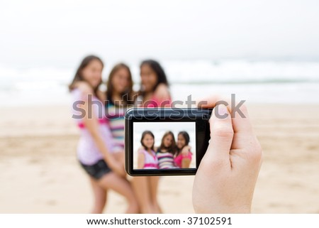 group of teen friends taking photos of each other