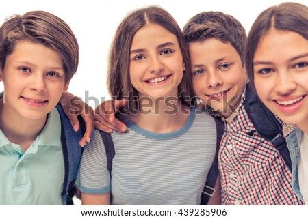 Group of teenage boys and girls with school backpacks is looking at camera and smiling, isolated on white