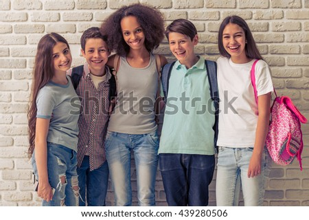 Group of teenage boys and girls with school backpacks is looking at camera and smiling, standing against white brick wall - stock photo