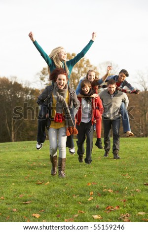 Group Of Teenage Friends Having Piggyback Rides In Autumn Landscape - stock photo