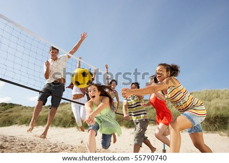 Group Of Teenage Friends Playing Volleyball On Beach - stock photo