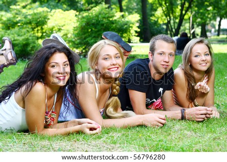 group of teenager boys and girls in the park - stock photo