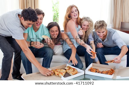 Group of teenagers eating pizza in the living-room on the sofa - stock photo