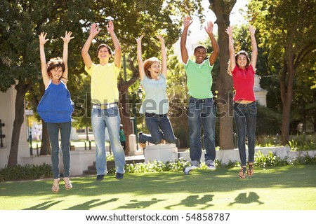 Group Of Teenagers Jumping In Air In Park - stock photo