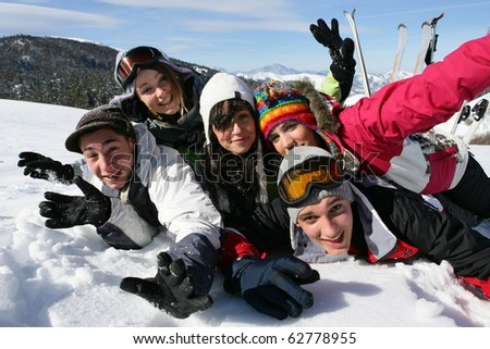 Group of teenagers laid in the snow - stock photo